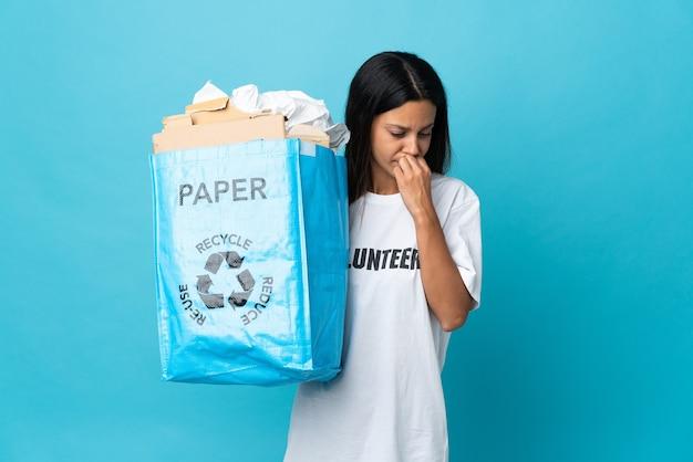 疑問を持っている紙でいっぱいのリサイクルバッグを保持している若い女性