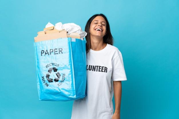 笑う紙でいっぱいのリサイクルバッグを保持している若い女性