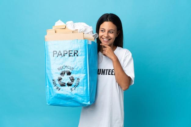 紙でいっぱいのリサイクルバッグを持って横を向いて笑顔の若い女性