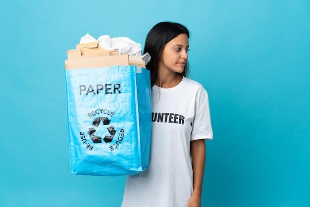 横を向いている紙でいっぱいのリサイクルバッグを保持している若い女性