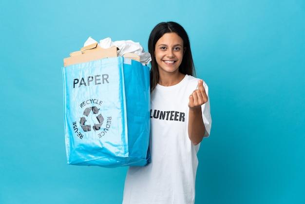 お金を稼ぐジェスチャーでいっぱいの紙のリサイクルバッグを持っている若い女性