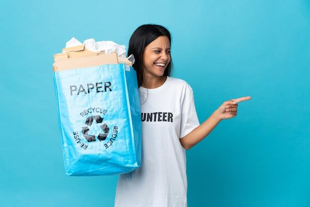 紙でいっぱいのリサイクルバッグを持って、指を横に向けて製品を提示する若い女性