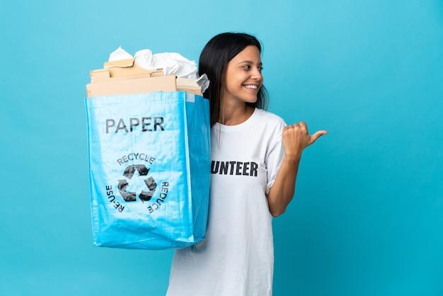 製品を提示する側を指している紙でいっぱいのリサイクルバッグを持っている若い女性