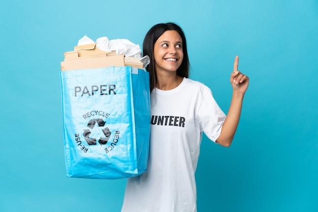 素晴らしいアイデアを指している紙でいっぱいのリサイクルバッグを持っている若い女性