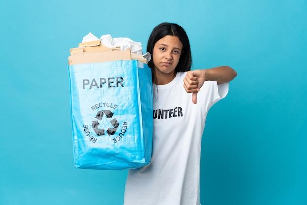 否定的な表現で親指を下に示す紙でいっぱいのリサイクルバッグを保持している若い女性
