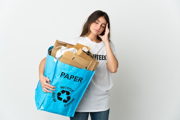 頭痛と白い背景で隔離のリサイクルする紙でいっぱいのリサイクルバッグを保持している若い女性