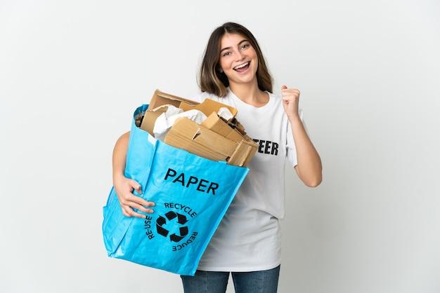 勝者の位置での勝利を祝う白で隔離のリサイクルする紙でいっぱいのリサイクルバッグを保持している若い女性