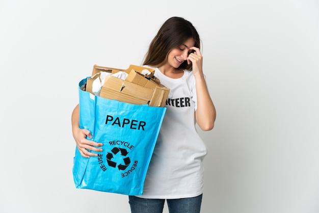 Молодая женщина, держащая мешок для рециркуляции, полный бумаги для переработки, изолирована на белом смеясь