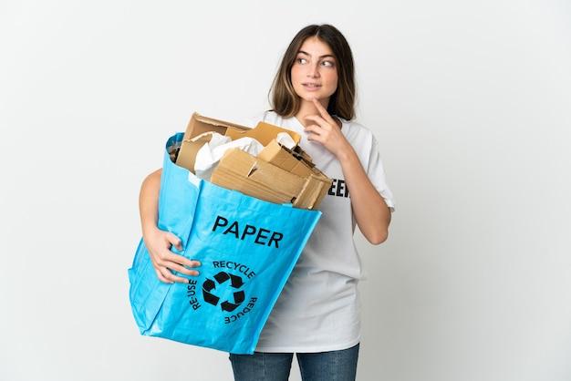 笑顔で見上げる白で隔離のリサイクルする紙でいっぱいのリサイクルバッグを保持している若い女性
