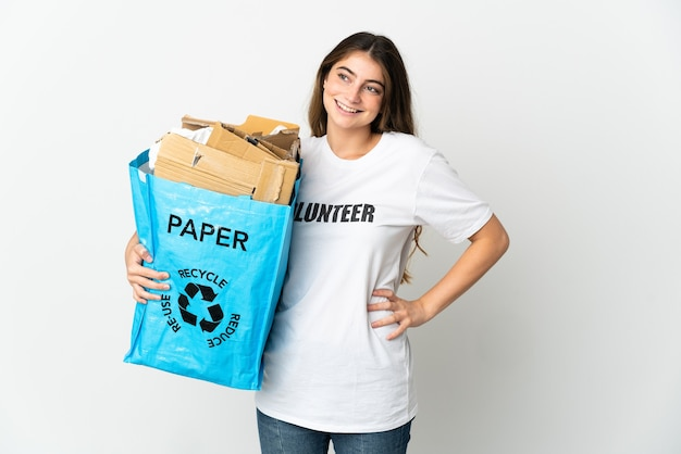 재활용 종이의 전체 재활용 가방을 들고 젊은 여자는 엉덩이에 팔을 들고 웃 고 흰색에 고립 된 재활용