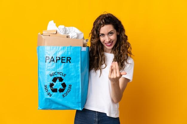 Молодая женщина держит мешок для переработки, полный бумаги для переработки