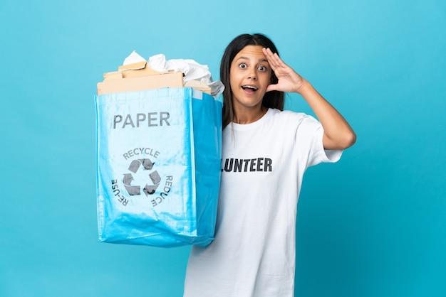 驚きの表情で紙でいっぱいのリサイクルバッグを保持している若い女性