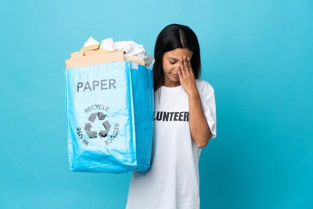 疲れて病気の表情で紙でいっぱいのリサイクルバッグを保持している若い女性