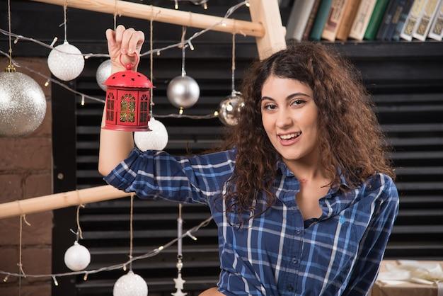 Молодая женщина, держащая красную рождественскую лампу