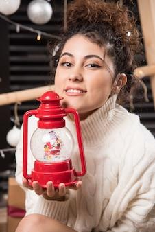 赤いクリスマスランプを保持している若い女性