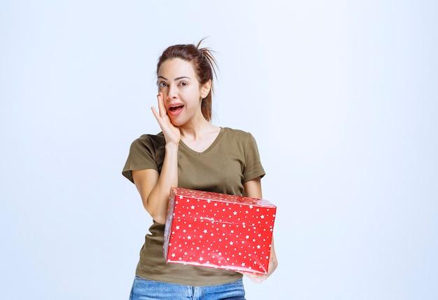赤いギフトボックスを持って、それをとても楽しんでいる若い女性