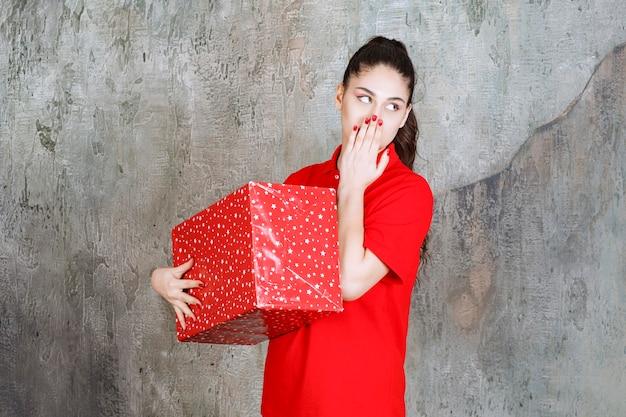 その上に白い点が付いている赤いギフトボックスを保持し、思慮深く見える若い女性。