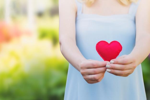 Молодая женщина держит красное сердце в руках