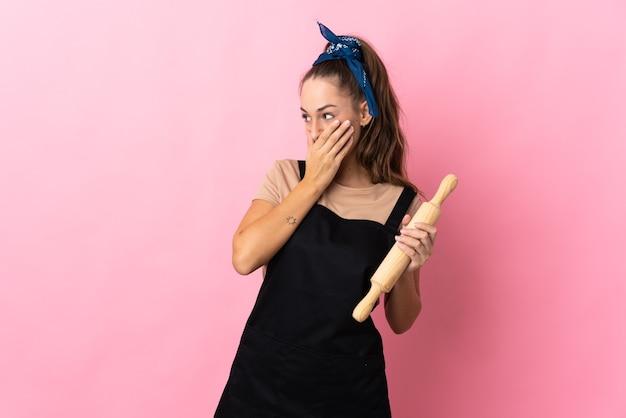 麺棒を持って口を覆い、横を向いている若い女性