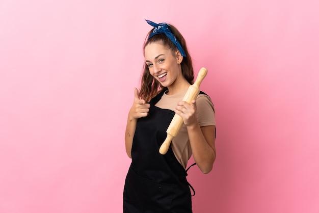 롤링 핀을 들고 앞을 가리키는 웃는 젊은 여자