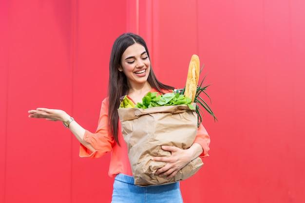 Молодая женщина, держащая сумку, полную овощных продуктов, молодая женщина, держащая продуктовый бумажный пакет, полный свежих овощей.