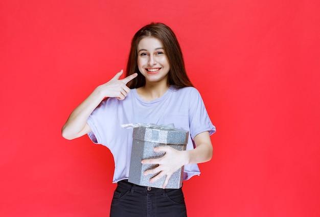 실버 선물 상자를 들고 행복 한 느낌이 젊은 여자.