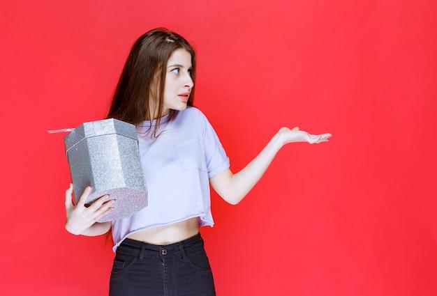 銀のギフトボックスを持って誰かを指している若い女性。