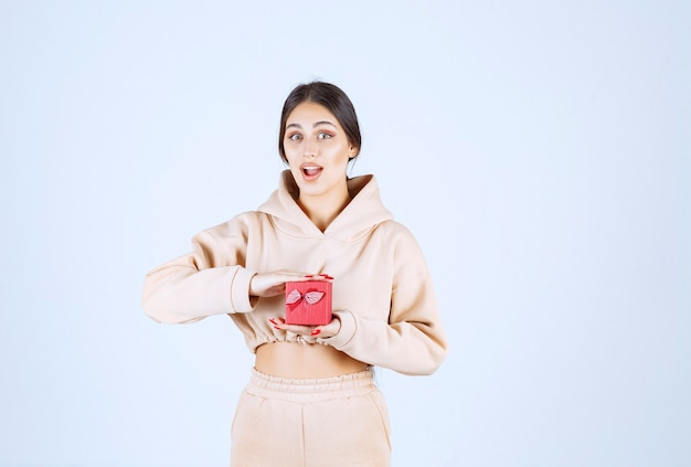 양손으로 작은 빨간 선물 상자를 들고 젊은 여자
