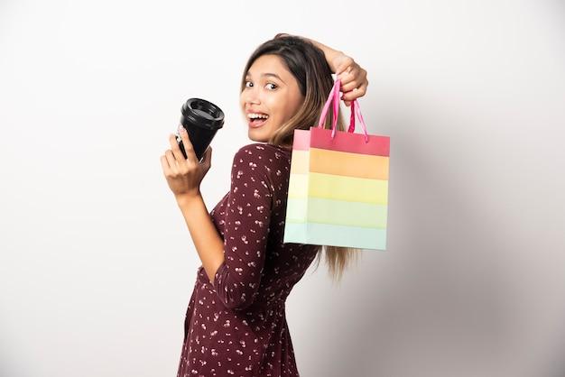 작은 쇼핑 가방과 흰 벽에 음료 한 잔을 들고 젊은 여자.