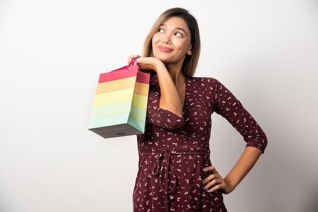 흰 벽에 작은 쇼핑 가방을 들고 젊은 여자.