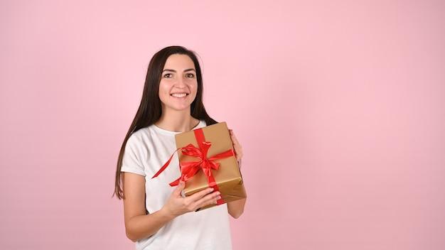 Молодая женщина, держащая улыбающийся подарок на розовом