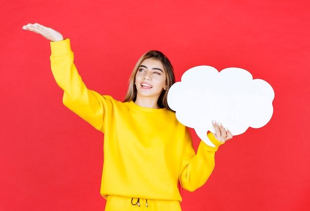 Молодая женщина, держащая речевой пузырь на красном