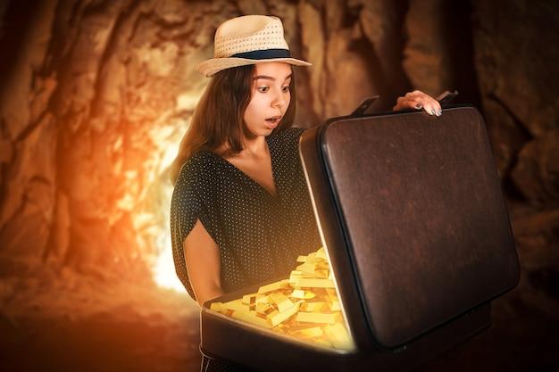 금괴가 가득한 가방을 들고 있는 젊은 여성.