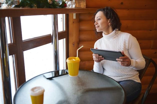 Молодая женщина держит планшет и смотрит в окно, сидя в деревянном кафе