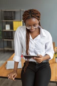 Молодая женщина, держащая планшет на работе