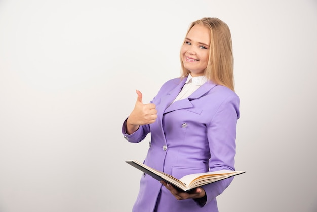 白でタブレットを保持している若い女性。