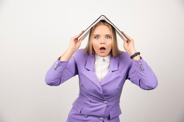 白の頭上にタブレットを保持している若い女性。
