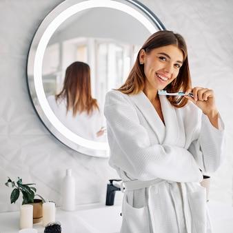 Молодая женщина, держащая зубную щетку