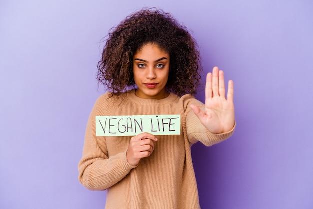 Молодая женщина, держащая плакат веганской жизни изолирована стоя с протянутой рукой, показывая знак остановки, мешающий вам