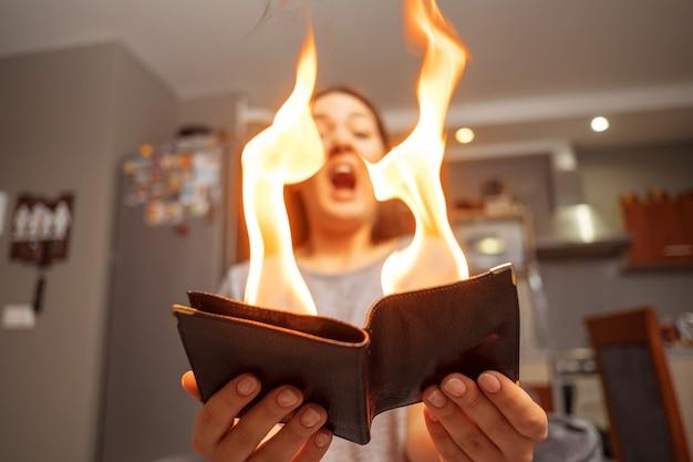 Молодая женщина, держащая бумажник, бумажник в огне, удивленная девушка, фокус волшебной концепции, бумажник горит огнем