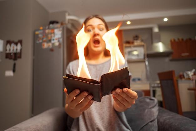 Молодая женщина держит кошелек, кошелек в огне,