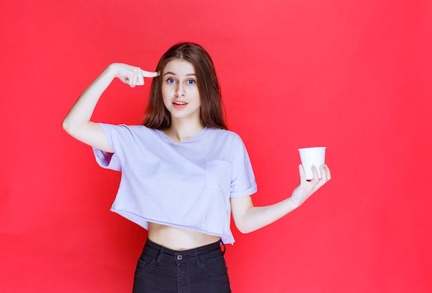白い使い捨ての水カップを持って考えている若い女性。