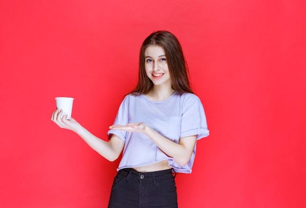Молодая женщина, держащая белый одноразовый стакан с водой.