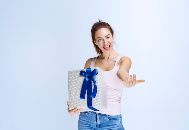 파란색 리본으로 포장된 흰색 선물 상자를 들고 옆에 있는 사람을 초대하여 선물하도록 하는 젊은 여성