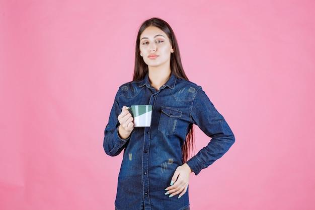 白緑のコーヒーマグを保持し、においがする若い女性