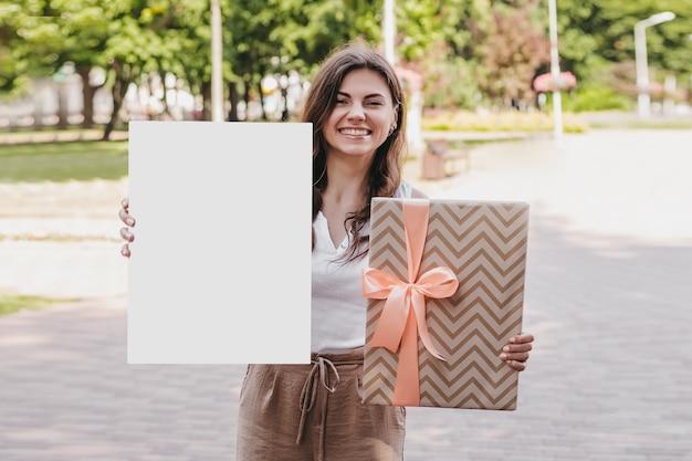 Молодая женщина держит в руках белый плакат и упаковку с бантом и улыбается на фоне парка