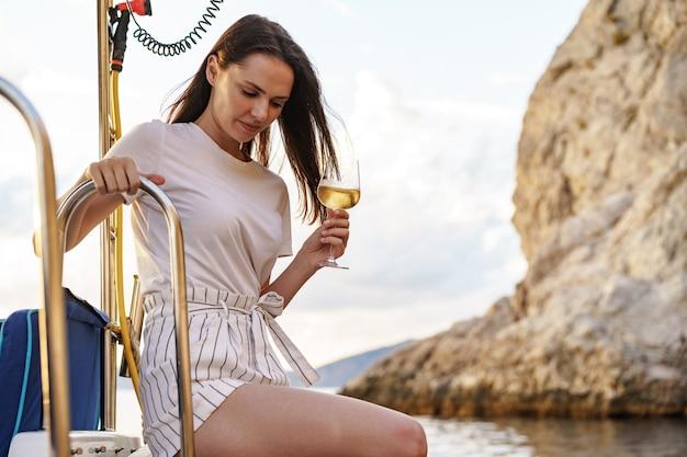 와인잔을 들고 세일링 요트의 갑판에 앉아 젊은 여자