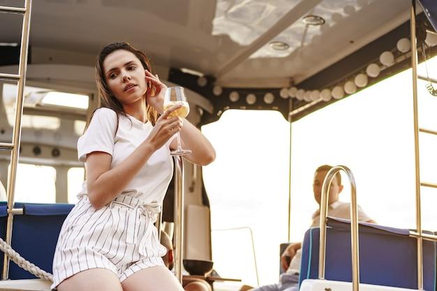 와인잔을 들고 요트 갑판에 앉아 있는 젊은 여성