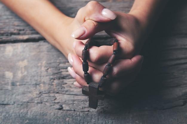 木製の十字架を保持している若い女性
