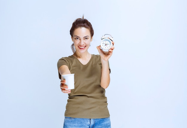 Young woman holding an alarm clock and a cup of drink pointing to the morning routine